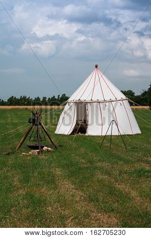 White Tent and Wooden Tripod for Bonfire on Meadow