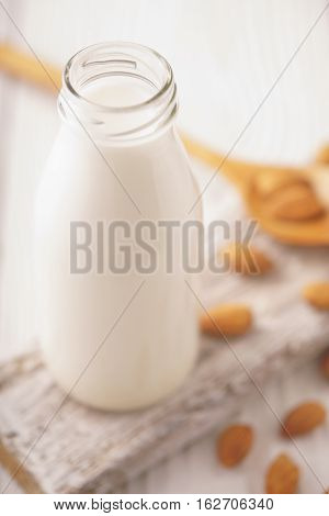 Almond milk in a glass bottle and almond nuts on a stand vertical