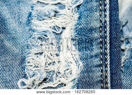 Holey jeans. Blue denim texture. Threads seam. Close-up.