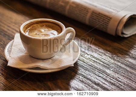 Coffee Cup And Newspaper On A Wooden Table. Good Morning Or Coffee Break Concept.