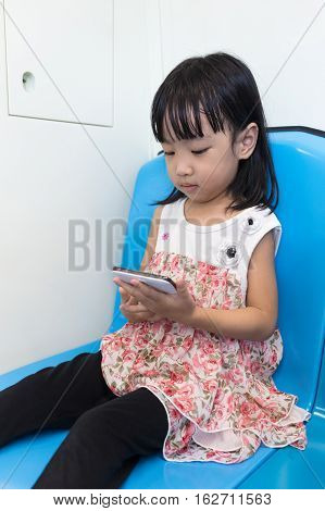 Asian Chinese Little Girl Sitting Inside A Mrt With Phone