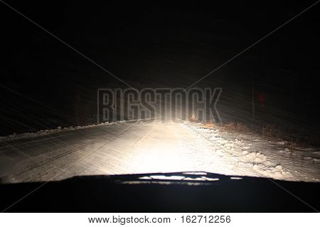 Real snow storm with strong wind. The night the road is illuminated only by car headlights. View from inside car.
