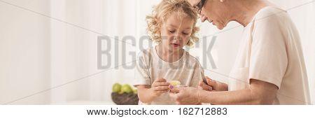 Grandma Helping Grandson In Kitchen