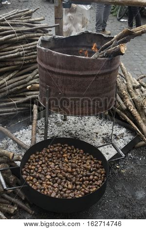 preparing roast chestnuts with brazier and embers