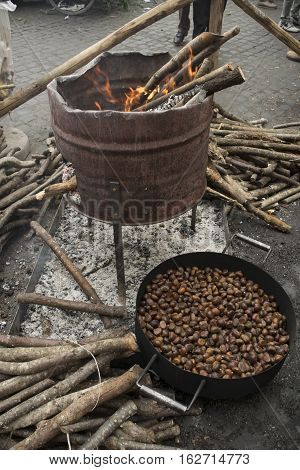 preparing street roast chestnuts with brazier and embers