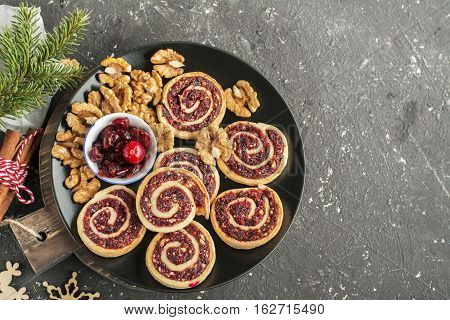 Cranberry nut swirl cookies on a white oval dish on New Year's treats with nuts, cranberries, fir branches. Top view