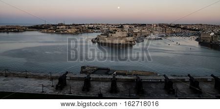 SCENE OF NIGHTFALL WITH THE MOON OVER THE HARBOR OF VALLETTA, MALTA AND CANNONS IN FOREGROUND