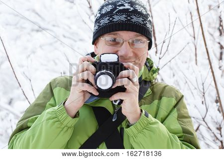 Smiling Man In Glasses, Green Sports Jacket And Ornamented Hat Stands In Winter Forest With Knitted