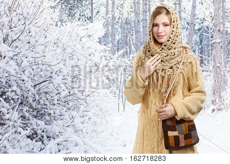 Young beautiful smiling stylish woman in openwork shawl and long beige sweater with checkered motley knitted bag stands in winter snowy forest.