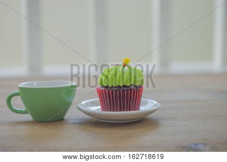 green cupcake and hot coffee on wooden table for new year birthday Christmas party celebration / cupcake and coffee