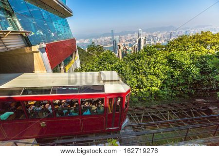 Hong Kong, China - December 10, 2016: The popular Peak Tram as he arrives at the terminus of Victoria Peak, the highest peak of Hong Kong island, with panoramic city skyline background. Sunny day.