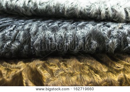 The fur is different colors of karakul pelts, lambskin texture, background