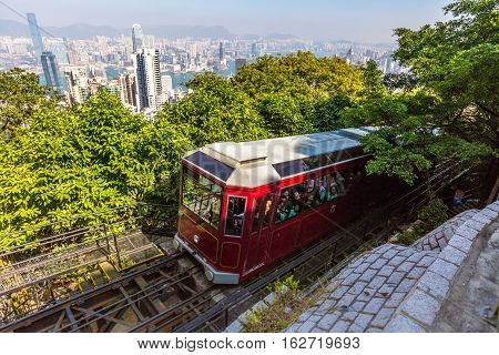Hong Kong, China - December 10, 2016: The popular red Peak Tram to Victoria Peak, the highest peak of Hong Kong island. Tourist tram with panoramic city skyline in the background in a sunny day.