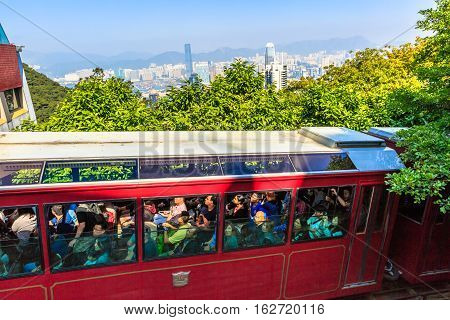 Hong Kong, China - December 10, 2016: The red Peak Tram to Victoria Peak, the highest peak of Hong Kong island. Close up of tram full of tourists, the most popular attraction in the city.