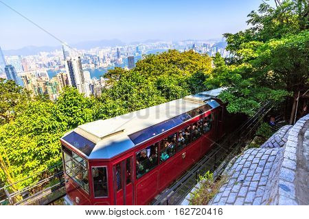 Hong Kong, China - December 10, 2016: The popular red Peak Tram as he arrives at the terminus of Victoria Peak, the highest peak of Hong Kong island, with panoramic city skyline background. Sunny day.