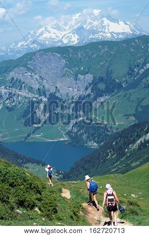 Three Hikers In Front Of Mont-blanc And Saint Guerin Lake In Savoy, France