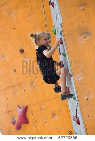 little girl climbing up the bouldering wall