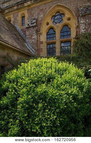 TIVERTON, DEVON, UK, 13 July 2016: Window in the wall of an Knightshayes Castle. Lots of by lush vegetation. Devon. UK