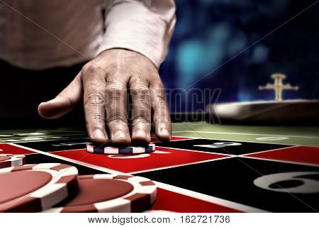gambler man bet on roulette number at casino