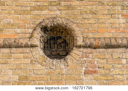 Ancient brick wall with round embrasure in Popov Castle located in town of Vasylivka Ukraine