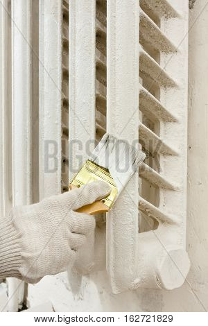 painting white radiator central heating with brush