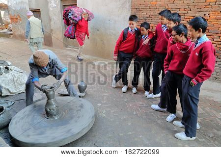 BHAKTAPUR, NEPAL - DECEMBER 30, 2014: Schoolboys watching a Potter at work in a busy street close to Potters Square