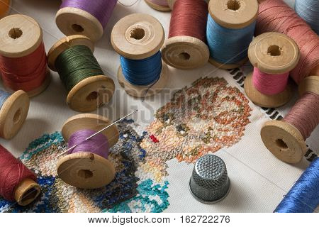 colored thread needle and thimble lying on embroidery