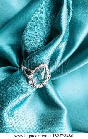 Elegant topaz ring on cyan crumpled satin as a background