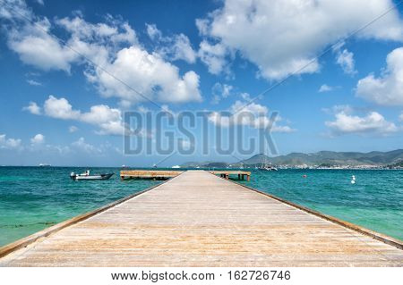 beautiful marine dock with wooden pathway harbour and boats transport on water sunny summer outdoor on cloudy blue sky background