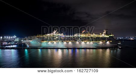 San Juan Puerto Rico - November 16 2015: Royal Cribbean cruise line ship Grandeur of the Seas standing in harbor with full bright illumination at night on water