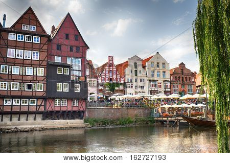 LUNEBURG GERMANY - November 23 2014: Historic old city and old harbour of Luneburg at evening with houses water cafe umbrellas and boat