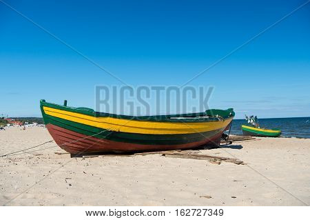 boat or ship modern marine vessel with colorful paint at moorage on sandy beach sunny outdoor on blue sea and sky background