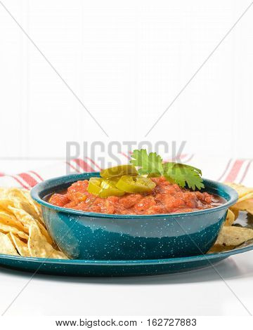 Bowl of spicy salsa garnished with jalapeno and cilantro.