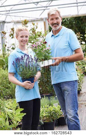 Portrait Of Staff At Garden Center Holding Plants