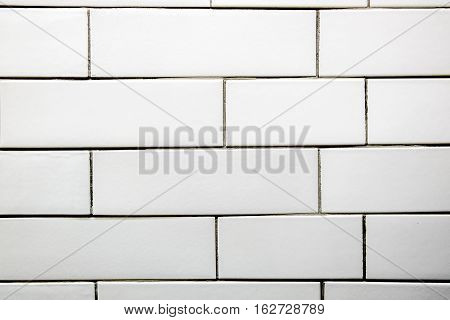 The wall is faced with white tiles with imitation of brickwork