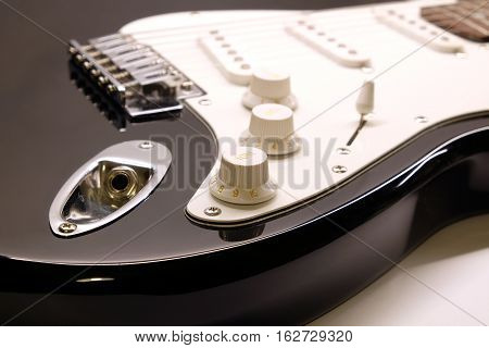 Part of modern electric six string guitar black color with glossy finish with empty metal jack, socket , pickups and control knobs isolated on white background horizontal view close up