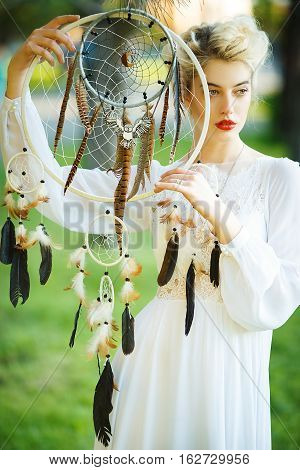 Outdoor portrait of a beautiful topmodel girl with dream catcher vintage and retro tone, soft focus. Full red lips.