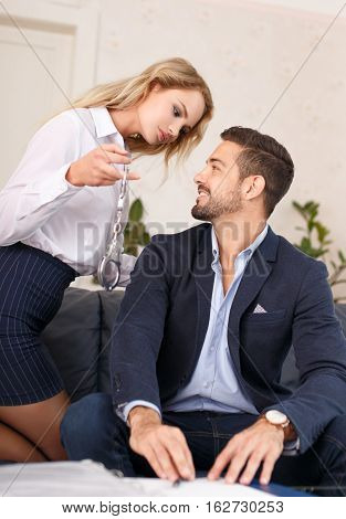 Secretary holding handcuffs for young rich CEO boss sexual harassment