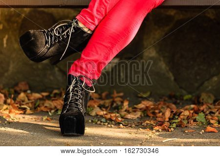 Female footwear. Part body woman wearing black elegant shoes high heels. Stylish girl in red trousers outdoor in park.