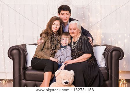 family happiness generation and people concept - happy family sitting on couch at home.