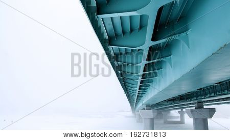 Under the bridge view in foggy weather in winter. Visible metal structure. The bridge goes into the perpective and dissolves into the mist.