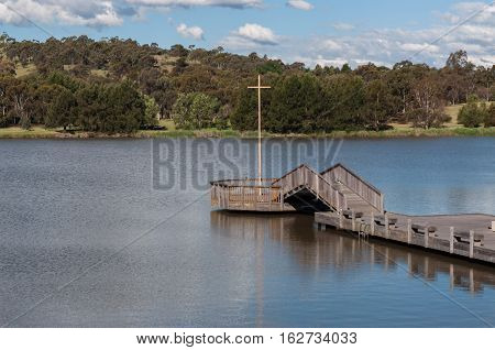 Canberra lake scene with wooden decking extending into water.