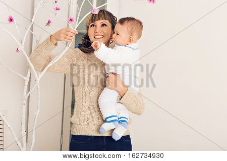 Mother and her child embracing with tenderness and care child giving mother flowers. Mother day concept happiness and love.