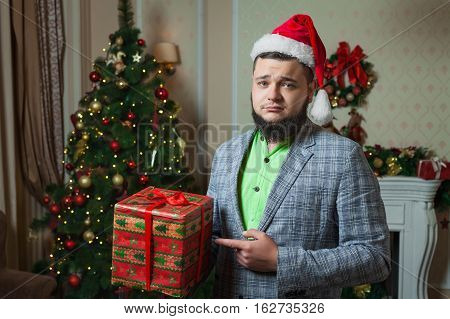 sad santa shows red box with a gift on the background of Christmas tree