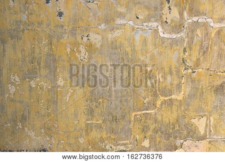 Old yellow painted cracked wall. Old abandoned wall background. Texture, pattern background. Yellow wall background