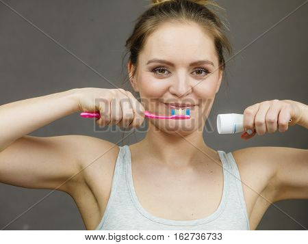 Woman holding brush and tooth paste for teeth cleaning. Happy funny smiling girl with toothbrush. Oral hygiene.