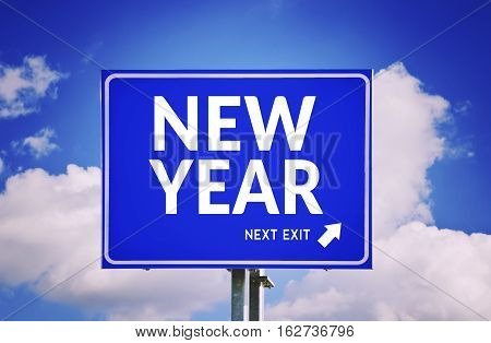 New year next exit road sign with sky background