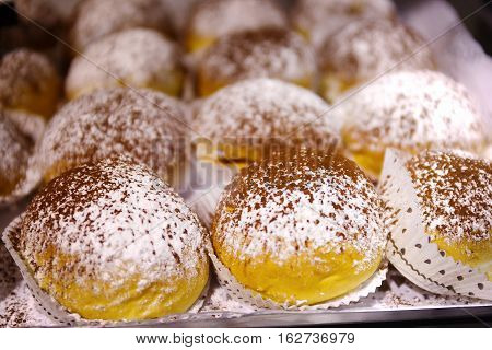 Filled donuts covered with powdered sugar and cocoa powder. by three series in the tray