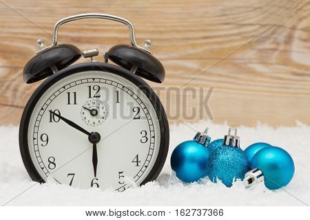 Winter Time Background Some snow Christmas ball ornaments and an alarm clock on weathered wood with copy space for your message
