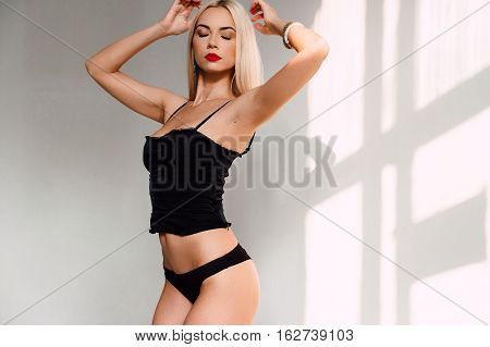 Beautiful Sexy Woman In Black Lingerie, In Underwear With Tan Skin And Red Lips Posing In Studio On